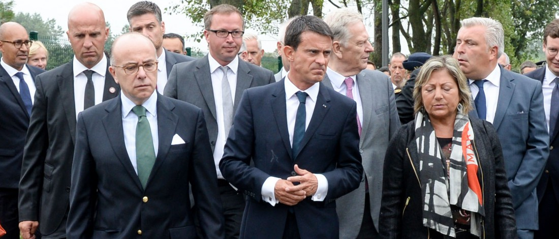 """French Prime Minister Manuel Valls (C) and French Interior Minister Bernard Cazeneuve (L) arrive in Calais, northern France, on August 31, 2015. Valls was set to meet EU officials in the refugee pinch point of Calais today as increasingly urgent efforts to deal with migration into Europe exposed divisions across the continent. France is expecting several million euros more in aid from Brussels, a government source said, to help deal with the thousands of migrants and refugees camped out in """"The Jungle"""" around the northern port, hoping to reach Britain. AFP PHOTO / POOL / DENIS CHARLET"""